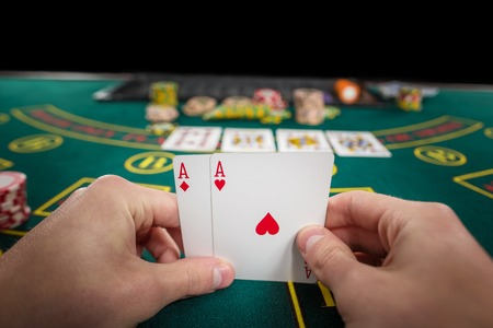 casino table: Male poker player holding the of two cards aces at green casino table