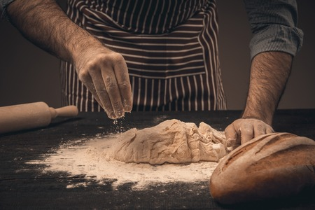knead: Male hands knead the dough. Chef cooking bread and bun Stock Photo