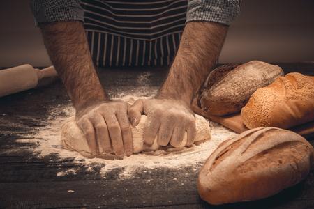 男性の手は、生地をこねます。シェフの調理パンとパン 写真素材