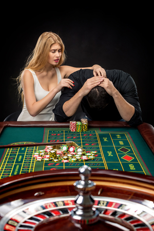 risky: Men with women playing roulette at the casino. Player follows the risky game