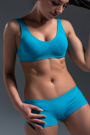 salud y deporte: Cierre de la imagen de la mujer en ropa deportiva relaja después de entrenamiento sobre fondo gris. cuerpo de la mujer muscular.