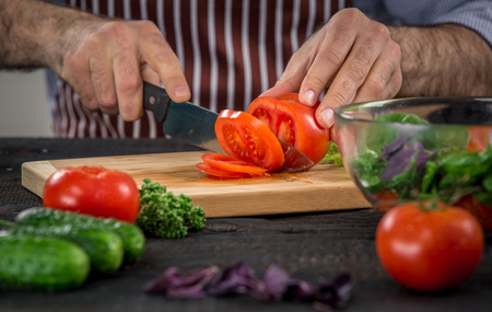 cuchillo de cocina: Close up en manos de los hombres de corte de tomate, que hace la ensalada. verduras de corte principales. estilo de vida saludable, alimento de la dieta Foto de archivo
