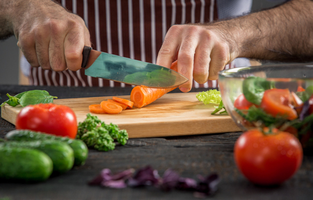 cuchillo de cocina: Close up on male hands cutting carrot, making salad. Chef cutting vegetables. Healthy lifestyle, diet food