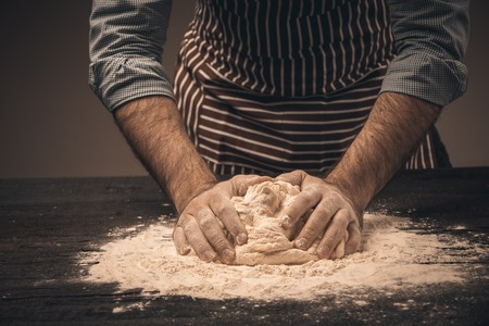 Male hands knead the dough. Chef cooking bread and bun Standard-Bild
