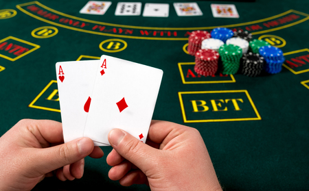 poker player: poker player holds cards. first-person view. two aces, a winning combination. male hands