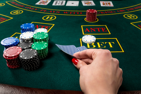 poker player: poker player holds cards. first-person view. female hand lifts the cards to see Stock Photo