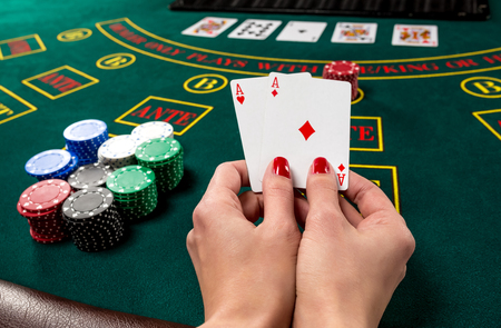 poker player: poker player holds cards. first-person view. two aces, a winning combination. female hands
