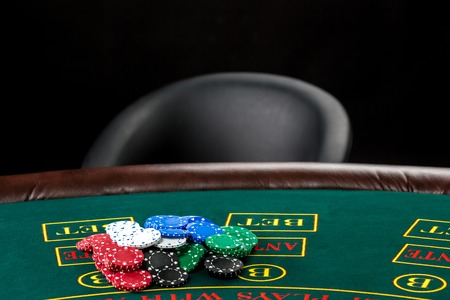 jack of clubs: Poker play. Chips on the green table and empty chair Stock Photo