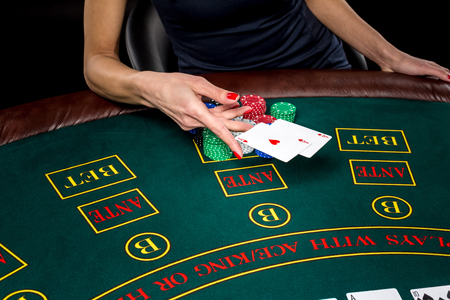 jack of clubs: Poker play. Chips and cards on the green table. Cards in a players hand. female hand throwing two aces. win Stock Photo