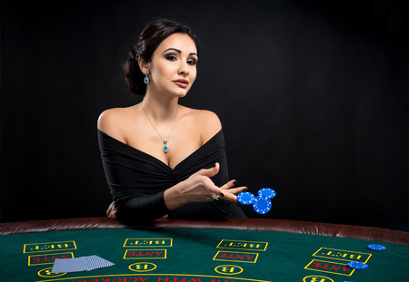 sexy woman with poker cards and chips. Female player in a beautiful black dress. girl sitting at the poker table and bets Stock Photo