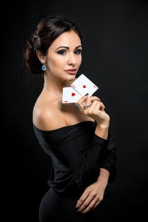 Sexy vrouw met pokerkaarten. Vrouwelijke speler in een mooie zwarte jurk. Twee azen Stockfoto