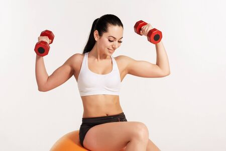 fitball: Young beautiful sportswoman in white top and black shorts with dumbbells exercising on fitball.