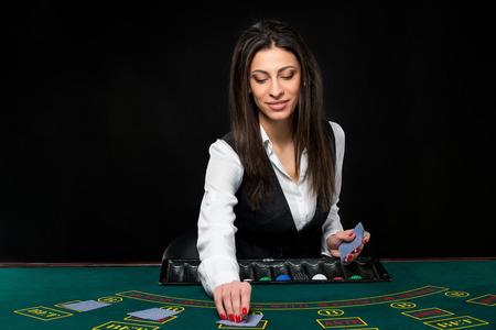 croupier: The beautiful girl, dealer, behind a table for game in poker. the dealer deals the cards.