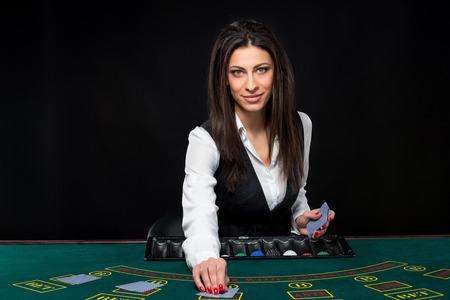 Het mooie meisje, handelaar, achter een tafel voor spel in poker. deelt de dealer de kaarten. Ze is op zoek naar de camera Stockfoto
