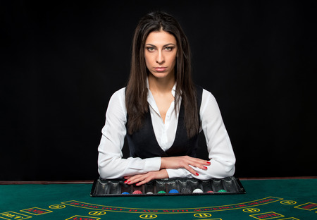 king and queen of hearts: The beautiful girl, dealer, behind a table for game in poker. She is looking at the camera Stock Photo