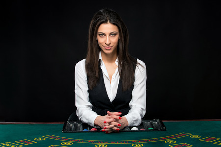 The beautiful girl, dealer, behind a table for game in poker. She is looking at the camera Stock Photo