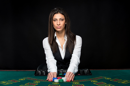 croupier: The beautiful girl, dealer, behind a table for game in poker, move chips