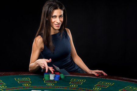 card player: sexy woman with poker cards and chips. Female player in a beautiful black dress. throws a card.