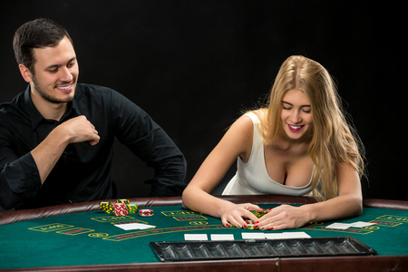winner man: Young couple playing poker and have a good time in casino, woman taking poker chips after winning Stock Photo