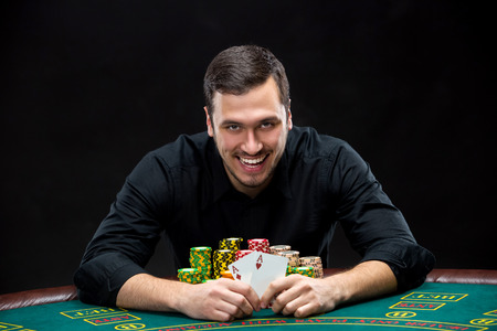 poker player: Happy poker player winning and holding a pair of aces sitting at a poker table with chips