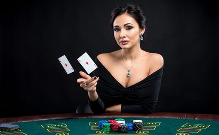 sexy vrouw met pokerkaarten. Vrouwelijke speler in een mooie zwarte jurk en het gooien van twee azen