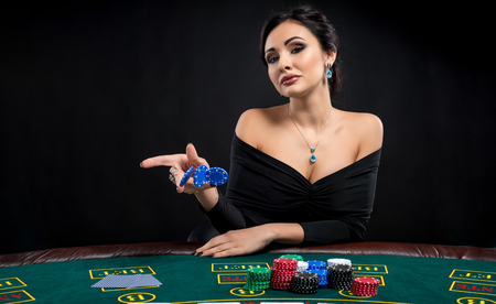 bets: sexy woman with poker cards and chips. Female player in a beautiful black dress. girl sitting at the poker table and bets Stock Photo