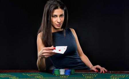 femme sexy avec des cartes de poker et des jetons. joueur Femme dans une belle robe noire, jette une carte. Deux aces