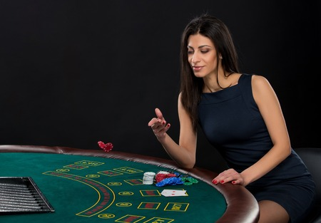 sexy woman with poker cards and chips. Female player in a beautiful black dress, bet chips