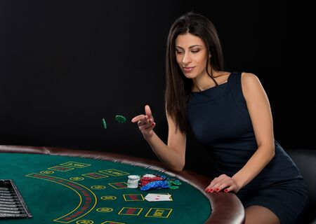 bet: sexy woman with poker cards and chips. Female player in a beautiful black dress, bet chips