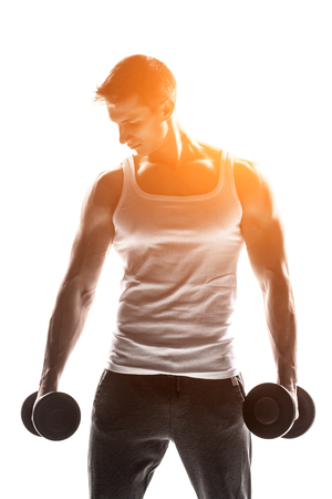 solar flare: Handsome muscular man with dumbbells looking at the camera, isolated on white background Whith solar flare Stock Photo