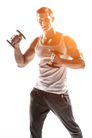 solar flare: Handsome muscular man doing exercises with dumbbells isolated on white background Whith solar flare
