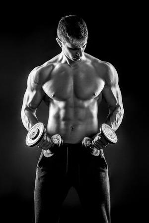 Machtige geschiktheidsmens die zijn gegrond lichaam met domoren ter beschikking op zwarte achtergrond tonen. Zwart-wit