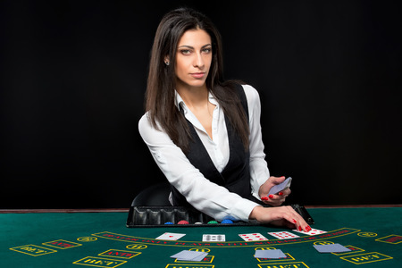king and queen of hearts: The beautiful girl, dealer, behind a table for game in poker. the dealer deals the cards. He is looking at the camera Stock Photo