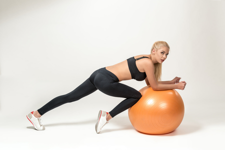 fitball: Young blonde woman training with fitball. she looks into the camera