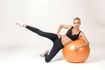 strengthen hand: Young blonde woman training with fitball. Fitness exercises. she looks into the camera Stock Photo