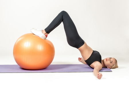 strengthen hand: Young blonde woman training with fitball on the mat. Fitness exercises