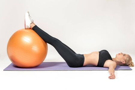fitball: Young blonde woman training with fitball on the mat. Fitness exercises