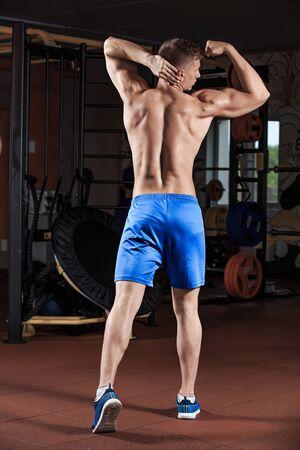 fitness hombres: Joven de pie fuerte en el gimnasio y flexionar los músculos. Atlética muscular del gimnasio culturista modelo posando después de ejercicios Foto de archivo