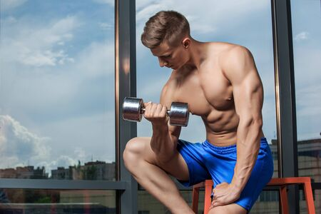 heavy weight: Muscular man doing heavy weight exercise for biceps with dumbbells in modern gym