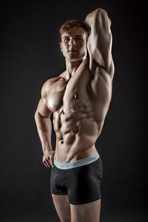 modelos desnudas: Muscular bodybuilder guy doing posing over black background. Naked torso in shorts. Foto de archivo