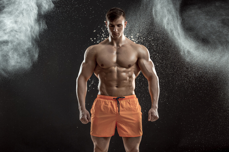 dynamically: young muscular man preparing to hand lifting heavy weight. White talcum dynamically scatters in different directions