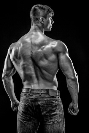 b w: Muscular bodybuilder guy doing posing over black background. He turned his back. Black and white, b w