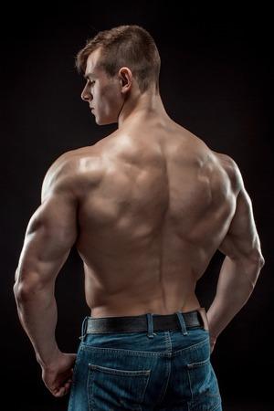 dorsi: Muscular bodybuilder guy doing posing over black background. He turned his back