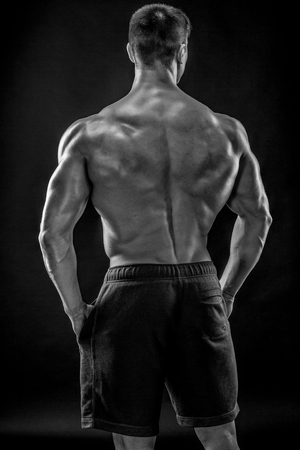 b w: Muscular bodybuilder guy doing posing over black background. He turned his back Black and white, b w