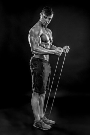 b w: Young athletic man exercising and doing fitness with a chest expander, resistance band, on dark background Black and white, b w Stock Photo