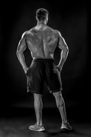 b w: Muscular bodybuilder guy doing posing over black background. He turned his back. full height Black and white, b w Stock Photo