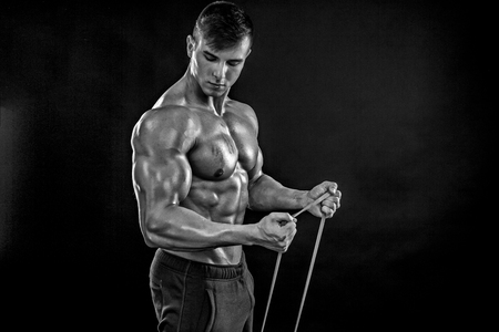 b w: Young athletic man exercising and doing fitness with a chest expander, resistance band, on dark background. Black and white, b w Stock Photo