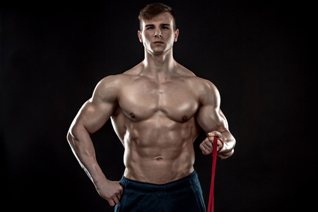 dorsi: Young athletic man exercising and doing fitness with a chest expander, resistance band, on dark background Stock Photo