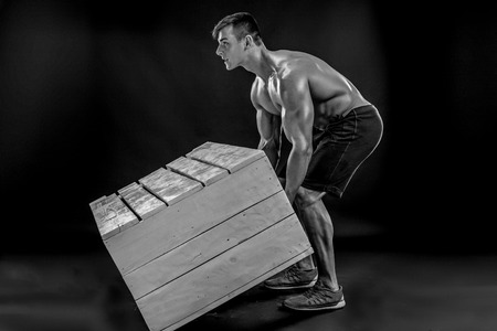 b w: Young Muscular man flipping box. Cross-fit exercise. Black and white, b w