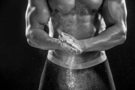 dynamically: young muscular man preparing to hand lifting heavy weight. White talcum dynamically scatters in different directions. Close-up. Black and white Stock Photo